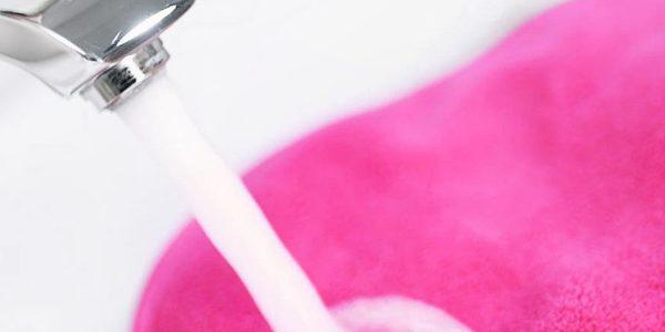 Make Up Radierer wird unter dem Wasserhahn angefeuchtet